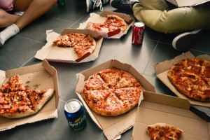 an array of pizzas in cardboard boxes and soda cans on the floor with people sitting cross-legged around the feast