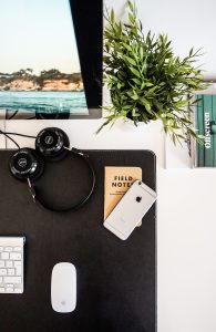 """a desk upon which is a cellphone placed diagonally over a notebook entitled """"Field Notes."""" Behind this, a monitor and a green, leafy plant."""